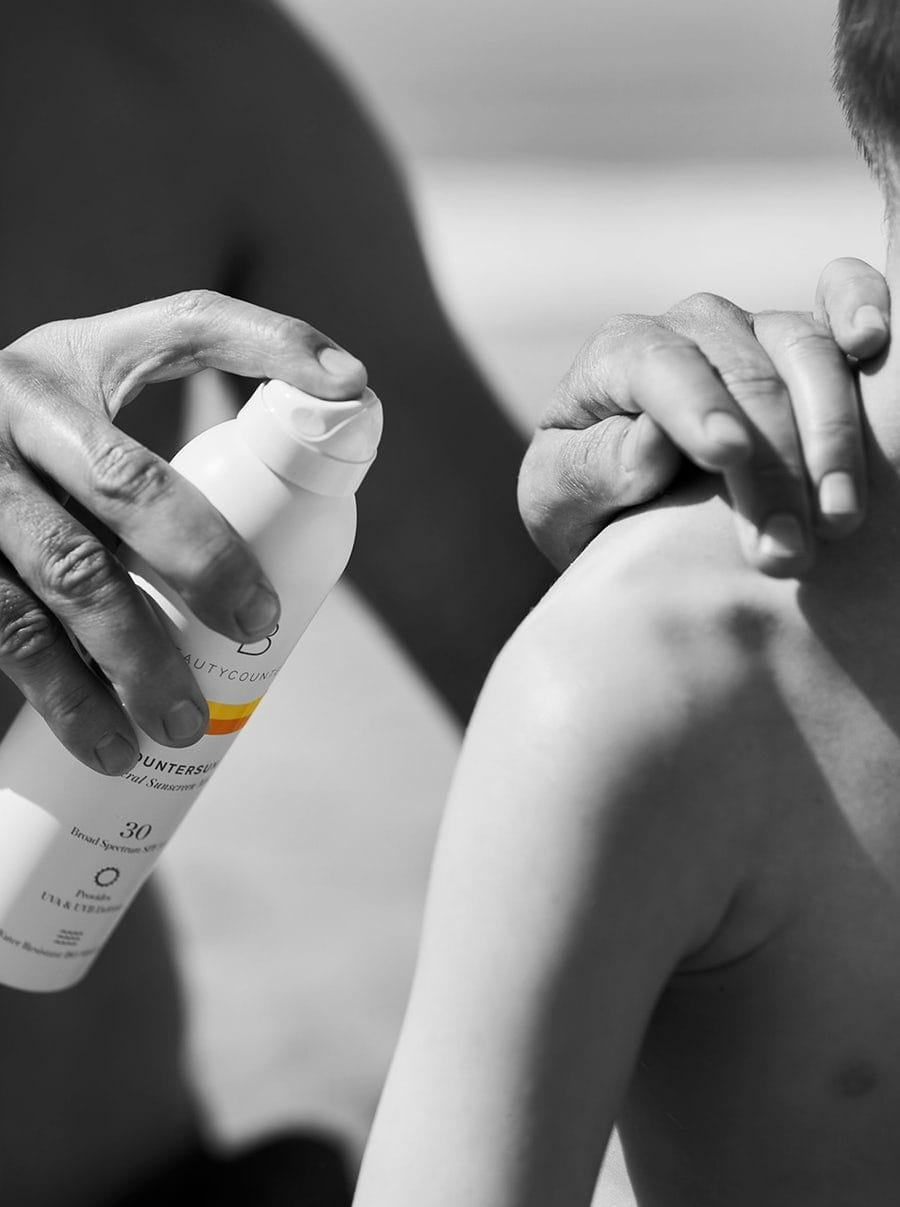 Adult applying Beautycounter sunscreen on child